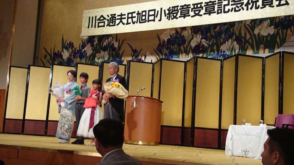 可愛い孫さんからお祝いの花束を受け取る川合夫妻