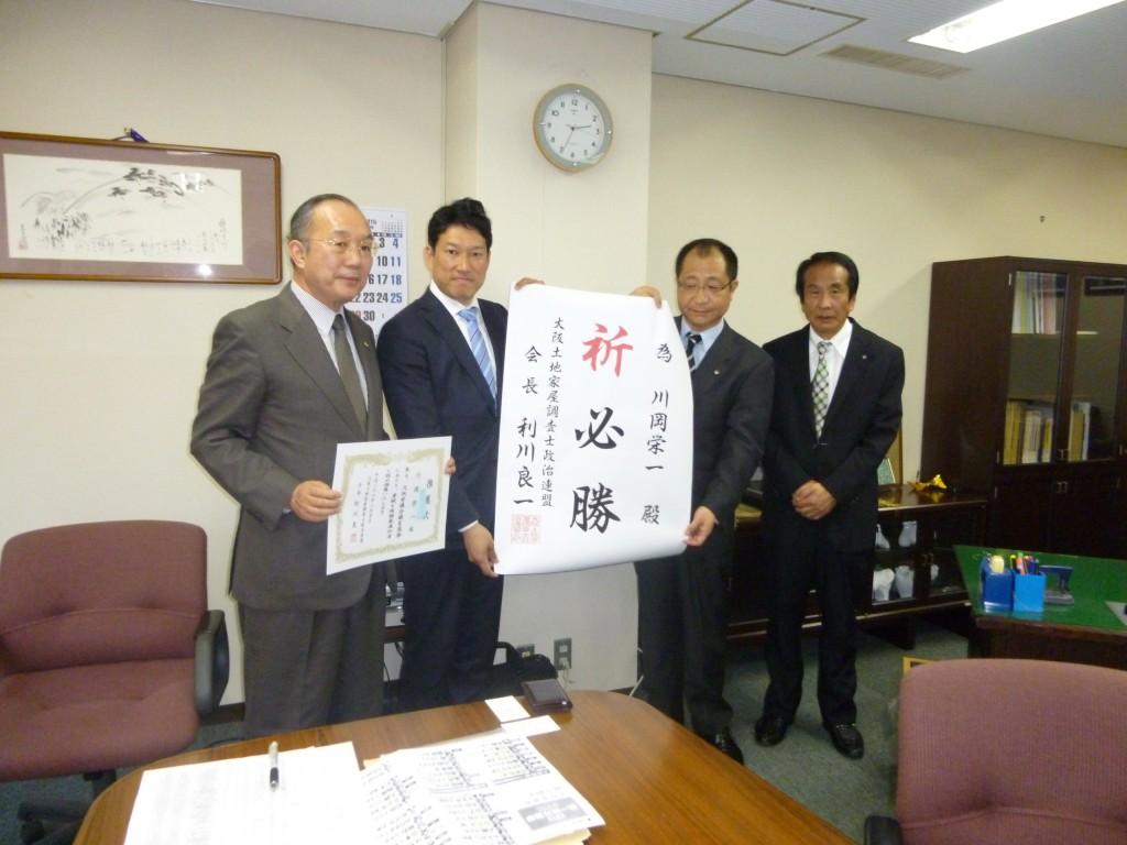 右から、加藤幸男大阪土地家屋調査士会長、利川良一政連会長、樋口尚也衆議院議員